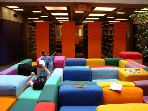 Student lounging on rainbow couches in Oberlin's Mudd library